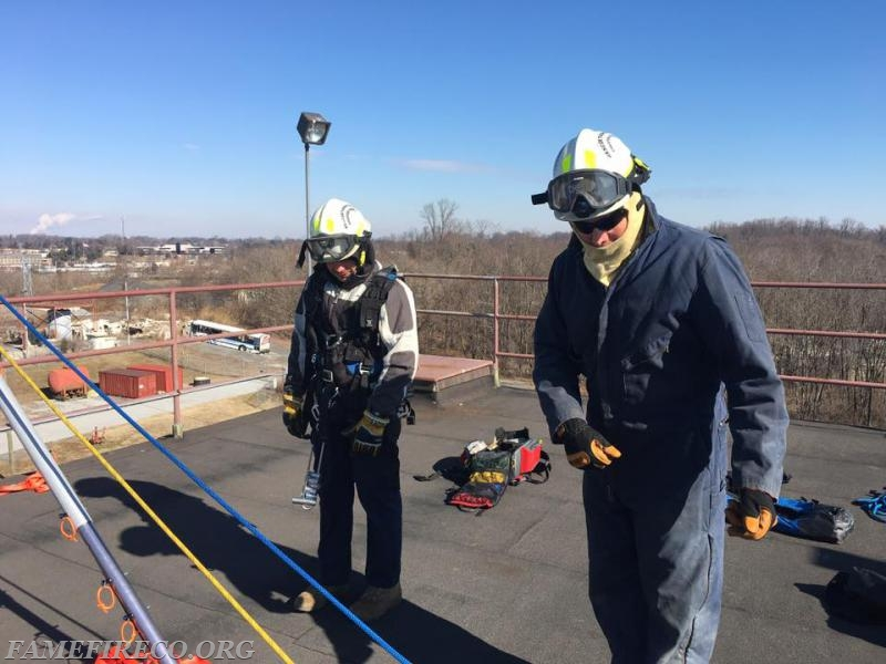 Technician Mark McCarthy (R) performs safety check prior to FF Cesar Lopez (L) rappelling.