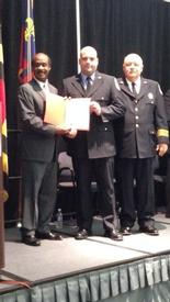FF McDonald receiving his diploma from Montgomery County Executive Isiah Leggett and Fire Chief Steve Lohr.